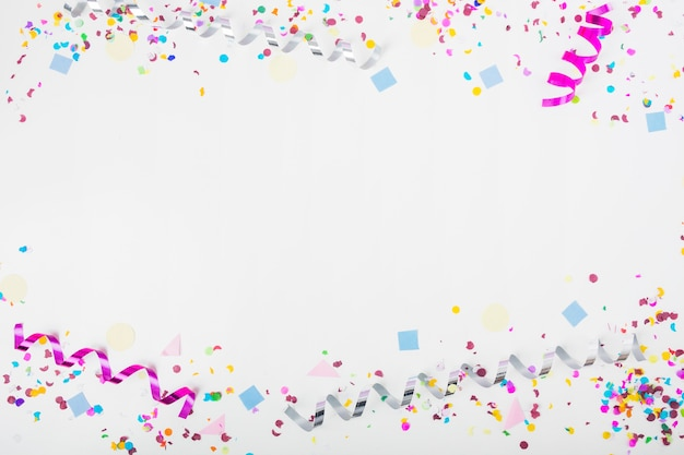 Верхняя и нижняя граница, сделанные с конфетти и скручивающими стримерами на белом фоне