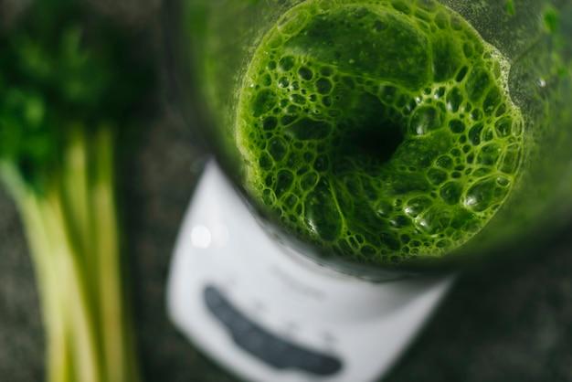 Верхний вид зеленого коктейля в блендере