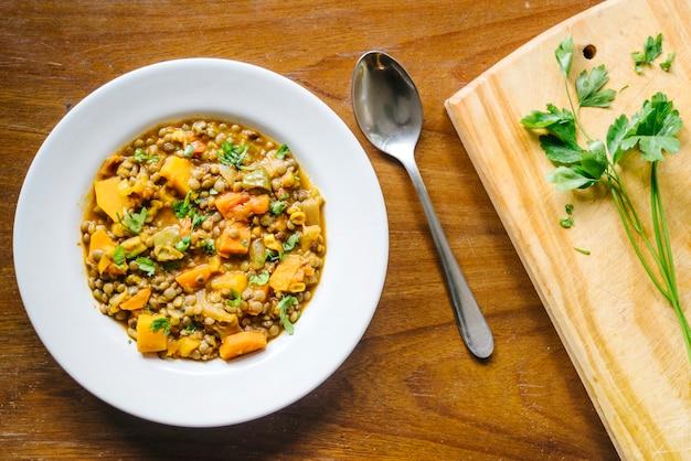 Вкусная еда на тарелке на деревянной столешнице