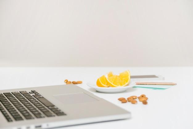 Ноутбук; миндаля и сладкой извести на белом столе