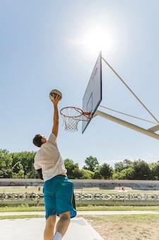 フープのボールを投げるバスケットボール選手の背面図