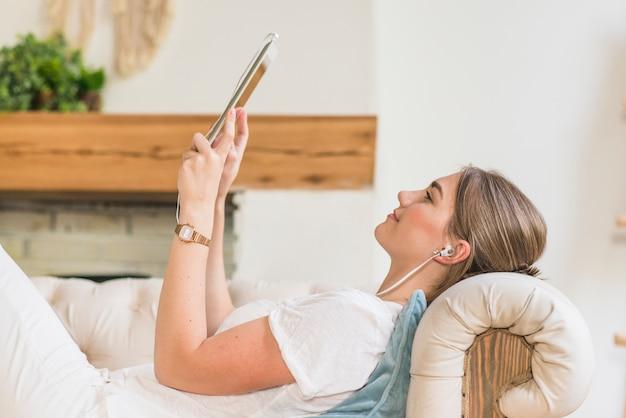デジタルタブレットを見ているヘッドフォンを着ている女性の側面図