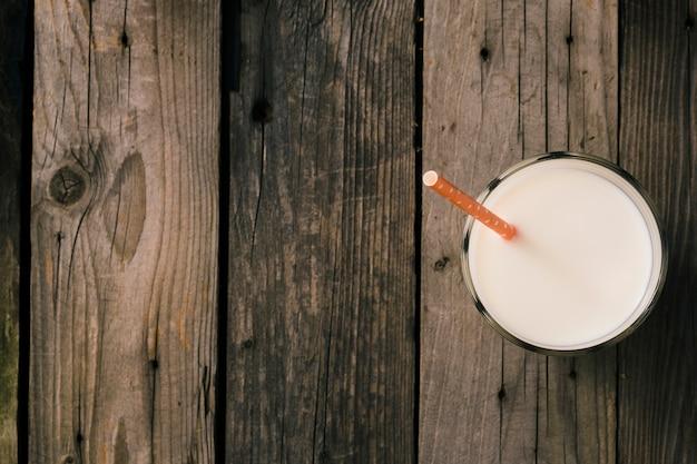 素朴な木製の背景の上にミルクのガラスのストロー