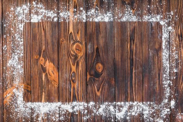 Белая мука над краем прямоугольной рамки на деревянном столе