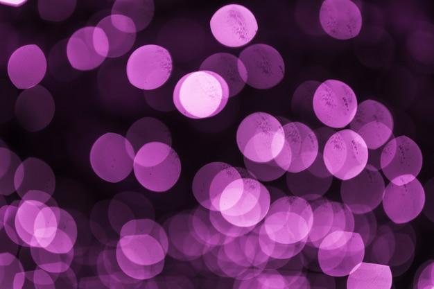 抽象的な紫色のデフォーカスされた円形の光の背景