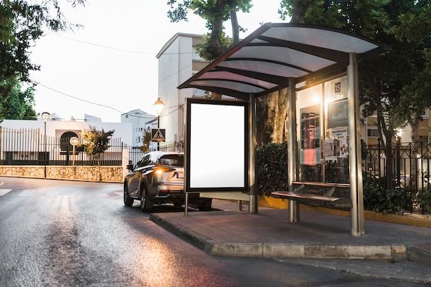 道路に白いポスターを置いた現代のバス停