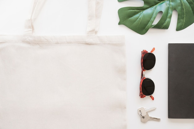 白い背景にサングラス、キー、トートバッグ、モンステラの葉のオーバーヘッドビュー