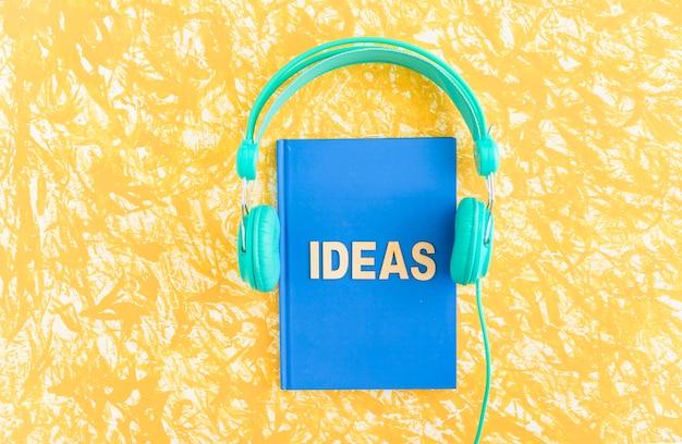 ヘッドフォン、黄色の背景にブルーカバーノートブックのアイデアテキスト