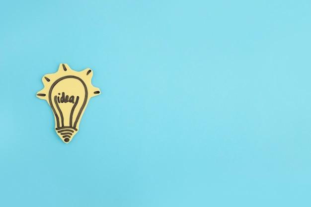 Освещенная идея лампочка, нарисованная на синем фоне