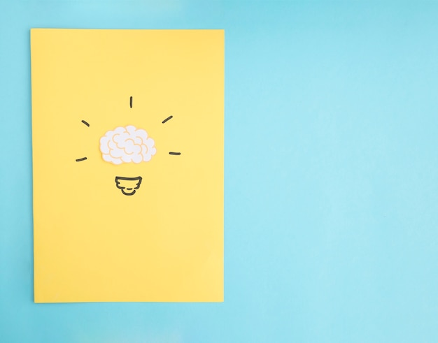 青い背景の上に黄色の紙の脳のアイデア電球