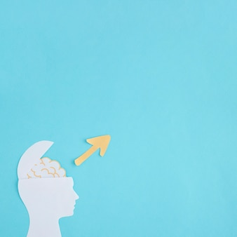 青い背景に開いた脳の紙の切り抜きの上に方向性黄色の矢印