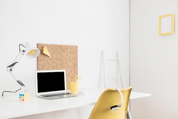 ホワイトルームのテーブルにモックアップのためのラップトップディスプレイ