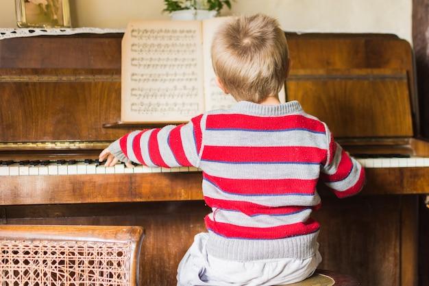 Вид сзади мальчика, играющего на классическом фортепиано