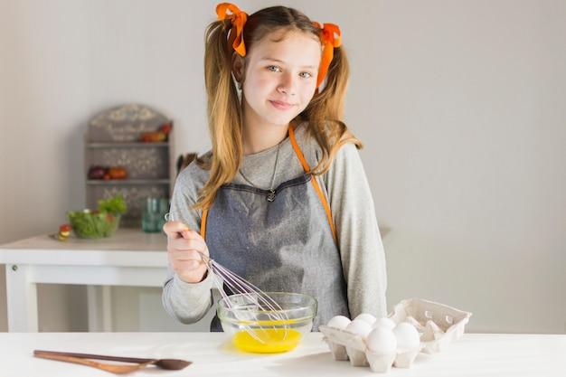 Девушка с фартуком, взбивающим яичный желток в миске на столе
