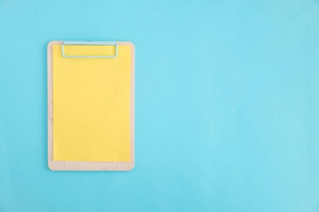 青い背景の上に木製のクリップボードに黄色い紙