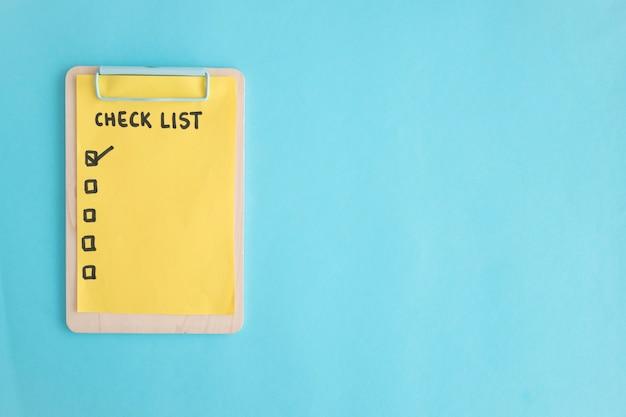青い背景の上に木製のクリップボードにリスト紙をチェックしてください