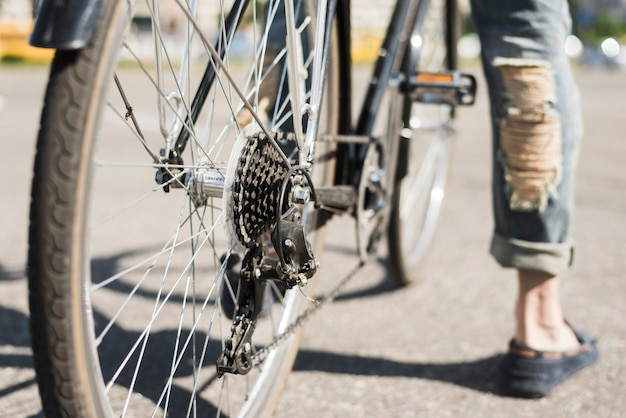 Крупный план велосипедного заднего колеса с цепью и звездочкой на дороге
