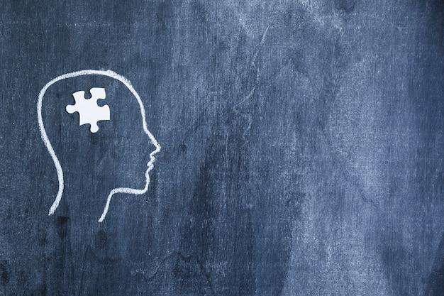 白いジグソーパズル、チョークで描かれた顔の輪郭