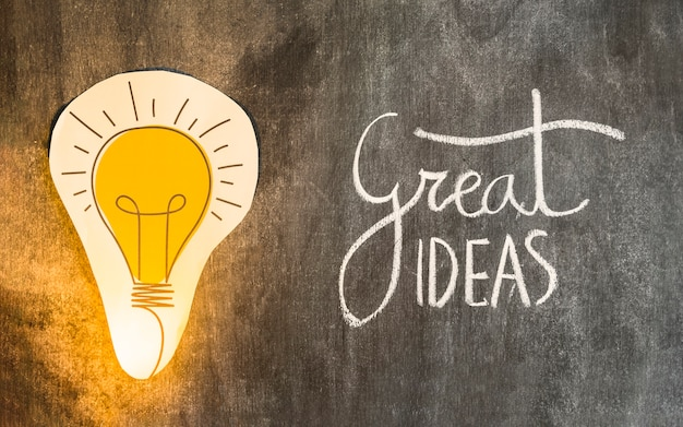 偉大なアイデアを持つペーパーカットアウト電球は、黒板にテキスト