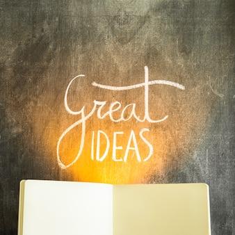 偉大なアイデアの上の光空白の開いた本を持つ黒板にテキスト