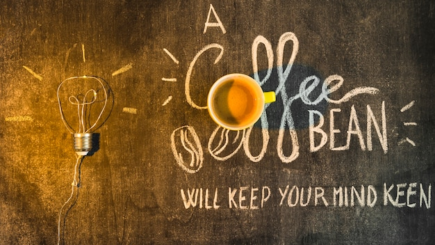 コーヒーカップの上のライトを黒板に書いたテキストで