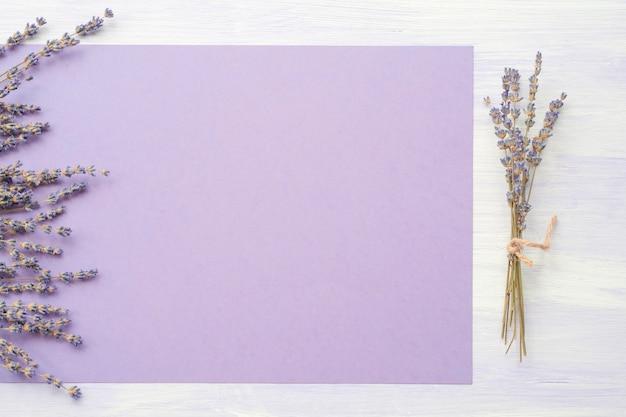 背景に紫色の紙の上にラベンダーの花