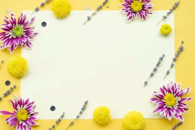 黄色の背景に空白の白い紙の上に花の装飾