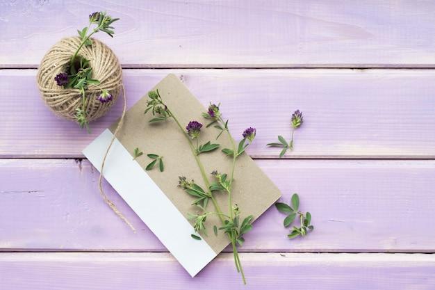 紫色の木製の背景に文字列のスプールで閉じたノートブックの花の小枝