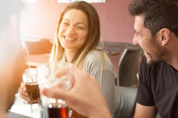 Пара, наслаждаясь напитком с друзьями
