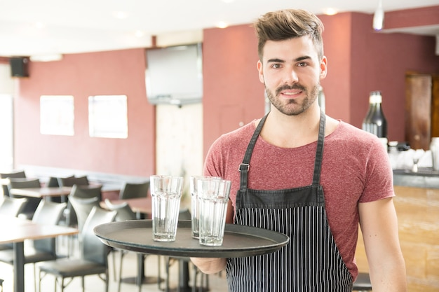 Мужской официант, держащий поднос с пустыми очками в баре
