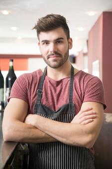バーに立っているエプロンを着た若い男の肖像