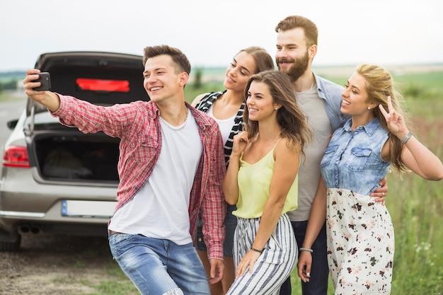 携帯電話でセルフを取って駐車した車の近くに立っている友人のグループ