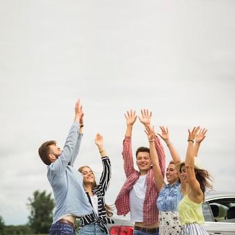 Счастливые друзья, подняв руки на открытом воздухе