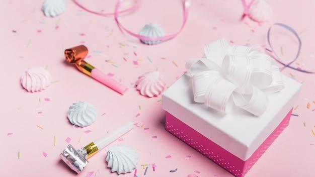 キャンディーのギフトボックス;振りかける。ピンクの背景にカールリボンとパーティーブロワー