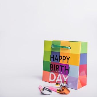 白い背景にパーティーブロワーとカラフルな誕生日の買い物袋
