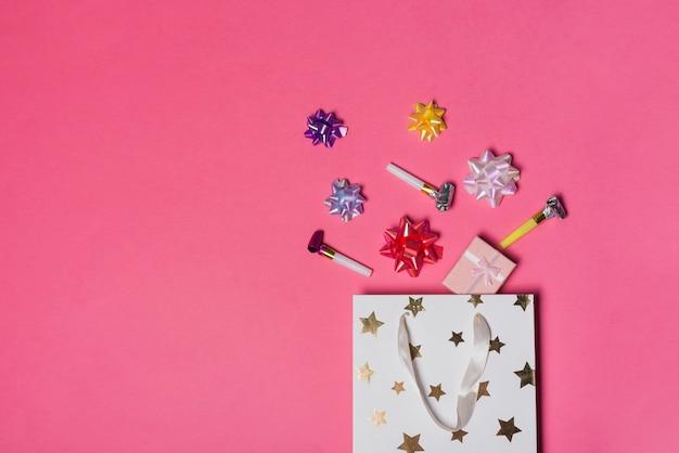 カラフルなサテンの弓;ピンクの背景に紙袋の上にギフトボックスとパーティーブロワー