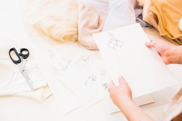 ファッションデザイナーは、テーブルの上に多くのファブリックを手にスケッチを保持