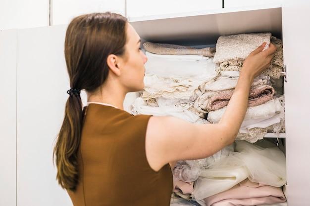 Молодая женщина-дизайнер, глядя на ткань в полке