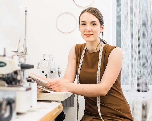 カメラを見ている若い女性の裁縫の肖像