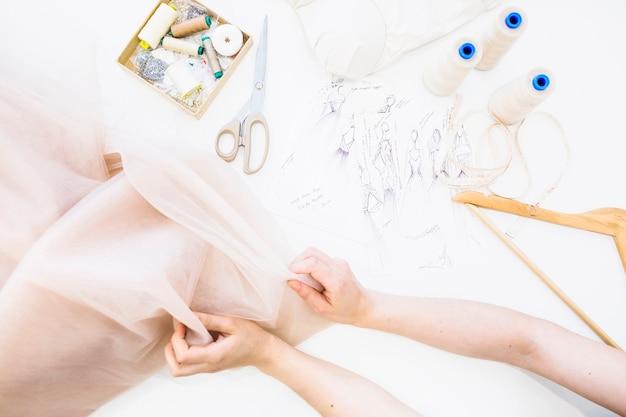 女性のデザイナーの手の上のファブリックを保持しているワークベンチ上の高められたビュー