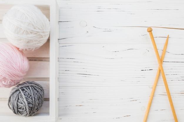 木製の表面上のかぎ針の近くの糸の多色のボール