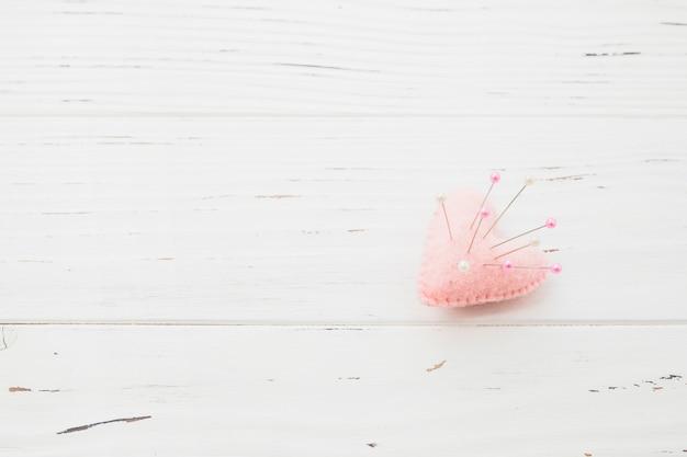 ピンクのハート型のクッションのピンを縫う