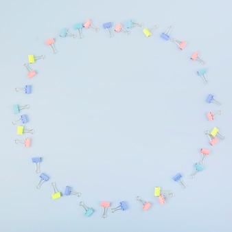 青色の背景に円を形成する様々なマルチカラーブルドッグクリップ