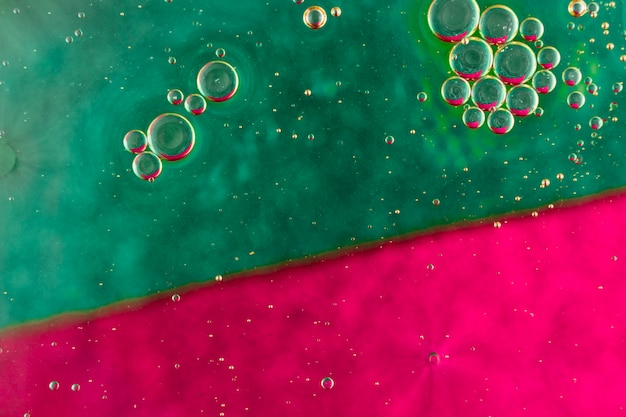 緑色と赤色の水面に浮かぶ球形の油泡
