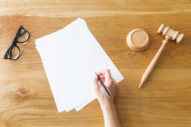 裁判官の手は木製の机の上にガーベルと眼鏡の近くに紙を書く