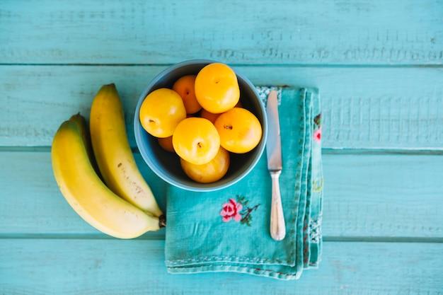 Повышенный вид на сливы и бананы на синем деревянном столе