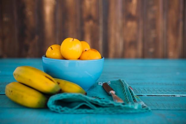 Бананы свежие сливы на синей деревянной поверхности