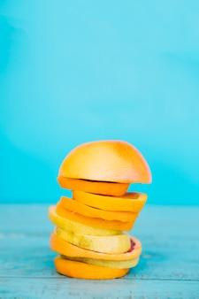青い木製の表面にオレンジとレモンの果物の積み重ねたスライス