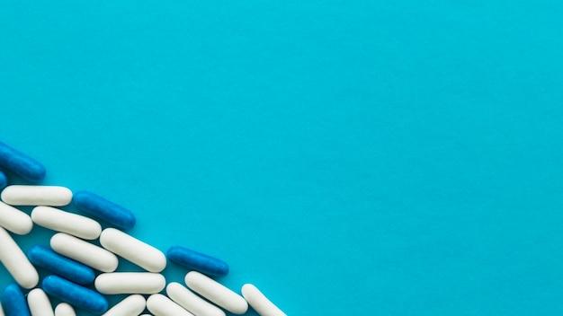 Повышенный вид белых и синих конфетных капсул на углу голубого фона