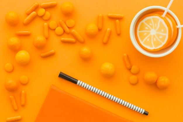 オレンジ色の表面に散らばったキャンディーを使ったペンとロリポップの高さ
